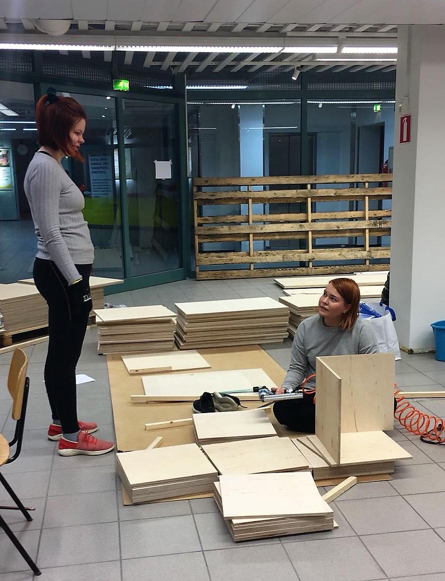 Sanni ja Aino rakentamassa myymäläkalusteita.